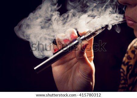 Close up of a woman inhaling from an electronic cigarette - stock photo