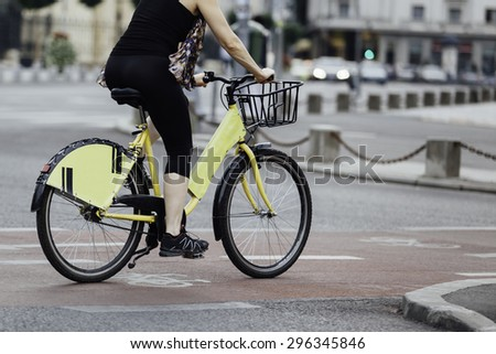 close-up of a woman legs on urban bike - stock photo