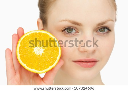 Close up of a woman presenting an orange against white background - stock photo