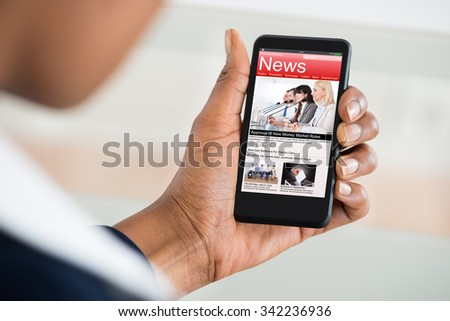 Close-up Of A Woman's Hand Reading News On Mobile Phone - stock photo