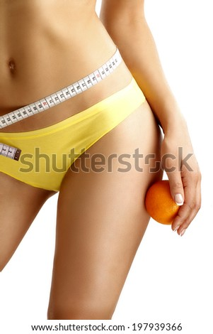 Close up of a woman showing hips with a fruit in her hand on white