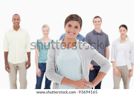 Close-up of a woman smiling with her hands on her hips with people behind against white background