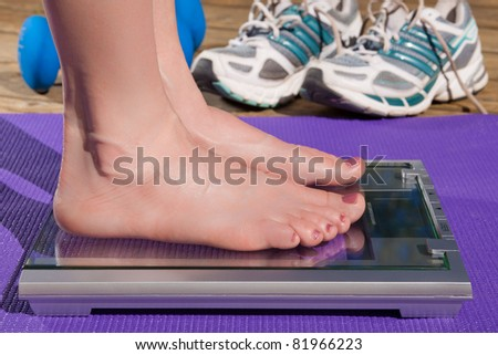 Close up of a woman standing barefoot on a scale. - stock photo