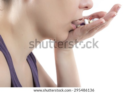 close up of a woman taking handful pills - stock photo
