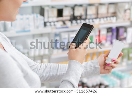 Close up of a woman taking picture of the product in drugstore - stock photo