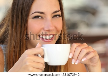 Close up of a woman tasting a coffee from a cup in a restaurant terrace with cream over lips - stock photo