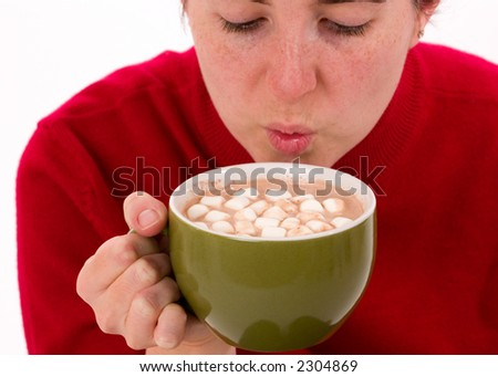 Close-up of a woman trying to cool a hot cup of cocoa by blowing on it. - stock photo