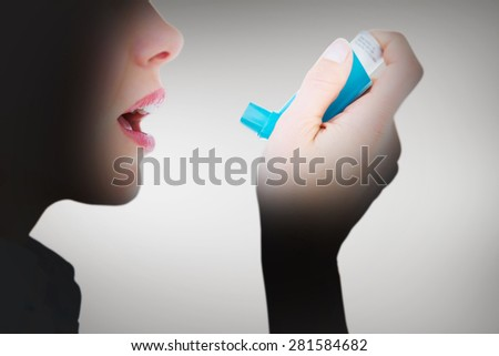 Close up of a woman using an asthma inhaler against grey vignette - stock photo