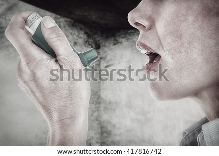 Close up of a woman using an asthma inhaler against image of room corner - stock photo