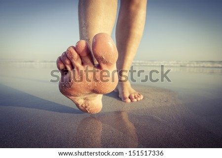 Close up of a woman walking on wet sand on the beach.