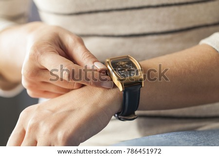 Close up of a woman winding her wrist watch