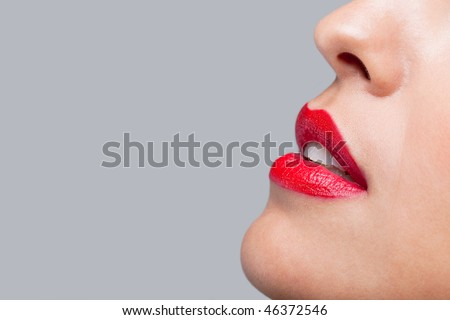 Close up of a womans face with bright red lipstick on her lips. - stock photo