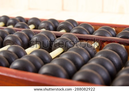 Close up of a wooden abacus beads. Selective focus, shallow depth of field. Wooden abacus on table wood texture background. - stock photo