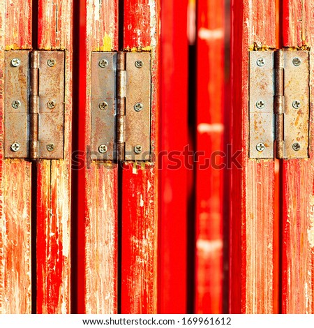Close-up of a wooden door red hinge - stock photo