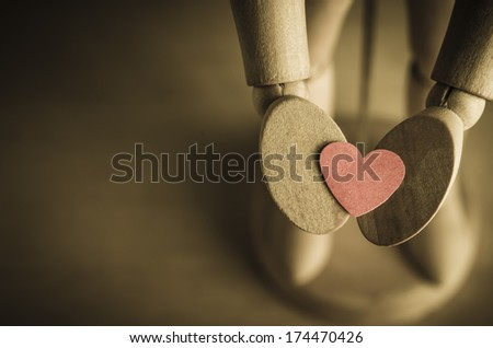 Close up of a wooden mannequin's hands, facing upwards and holding out a red, paper heart to represent an offer of love or Valentines Day.  Processed with vintage finish with copy space on left side. - stock photo