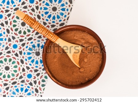 close up of  a wooden spoon and chocolate powder on blue background - studio shot  from above - stock photo