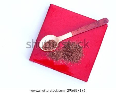 close up of  a wooden spoon and chocolate powder on red background - studio shot  from above - stock photo