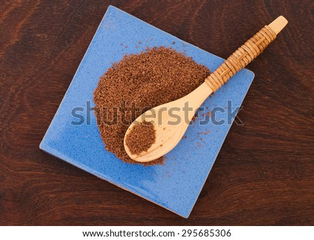 close up of  a wooden spoon and chocolate powder on wooden background - studio shot  from above - stock photo