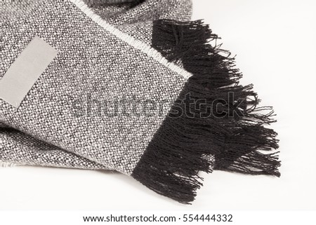 Close up of a wool scarf with empty tag  and black tassels  on white background, scarf top view.