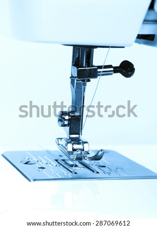 Close-up of a working part of the sewing machine. Toning in blue.