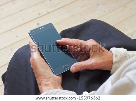 Close up of a wrinkled finger touching a mobilephone - stock photo