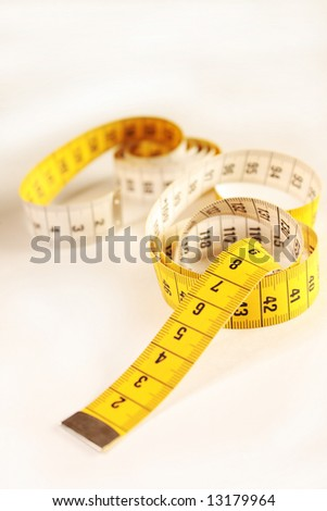 Close up of a yellow measuring tape - stock photo