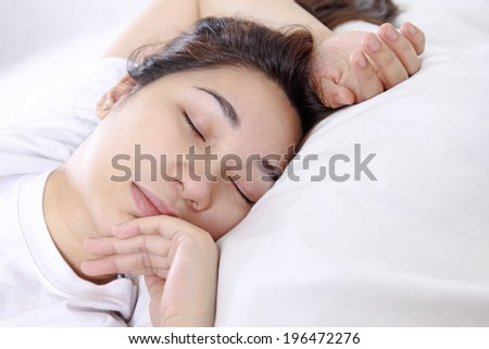 Close up of a young asian lady sleeping peacefully. - stock photo