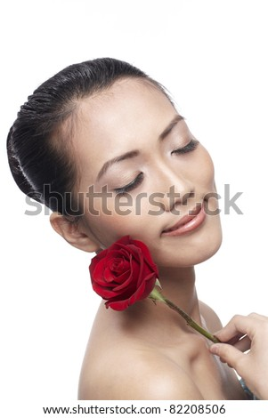 Close-up of a young Asian woman holding a flower