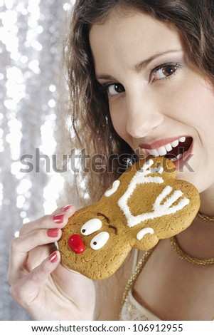 Close up of a young attractive woman biting a Christmas decorated buiscuit.