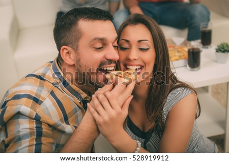 Close up of a young beautiful couple sharing pizza cut.