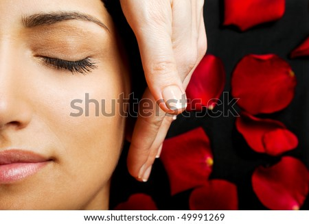 close up of a young beautiful face receiving massage at spa - stock photo