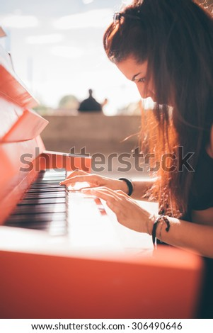 Close up of a young beautiful reddish brown hair caucasian girl playing piano - creative, performance, music concept - she is dressed with a black shirt and plays a red piano - stock photo