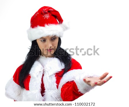 Close-up of a young brunette woman dressed in Santa Claus, holding out her hand ,advertising,promoting.Isolated on white background. - stock photo