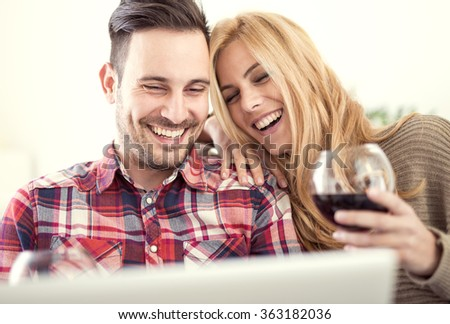 Close up of a young couple enjoying wine at home.They are sitting close to each other and drinking red wine.Love concept. - stock photo