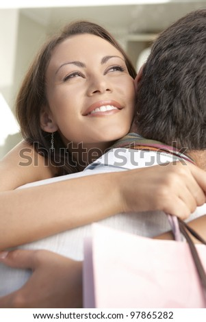 Close up of a young couple hugging with shopping bags.