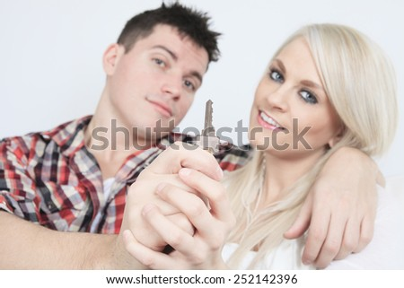 Close-up of a young couple receiving their new car's key sitting on a sofa - stock photo