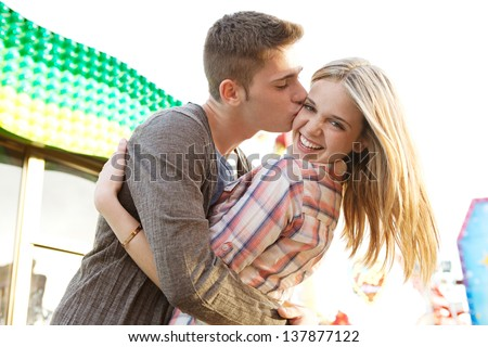 Close up of a young couple visiting an amusement park arcade with man kissing the girl on the cheek during a sunny day. - stock photo