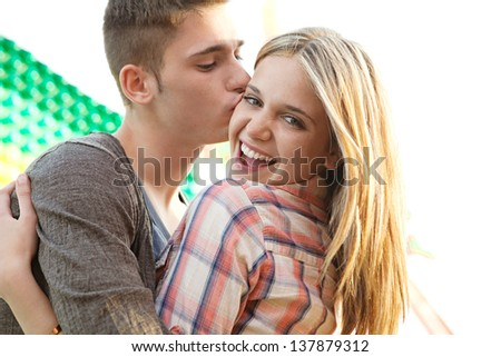 Close up of a young couple visiting an amusement park arcade with man kissing the girl on the cheek during a sunny day.