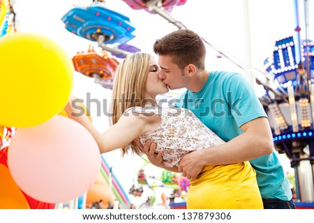 Close up of a young couple visiting fun fair park arcade being romantic and kissing during an early evening with lights and rides in the background. - stock photo