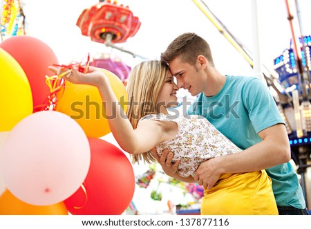 Close up of a young couple visiting fun fair park arcade being romantic during early evening with lights and rides in the background. - stock photo