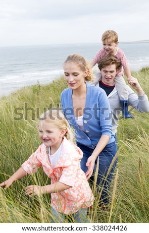 Close up of a young family of four walking through long grass next to the beach. They are wearing casual clothing and are smiling.  - stock photo