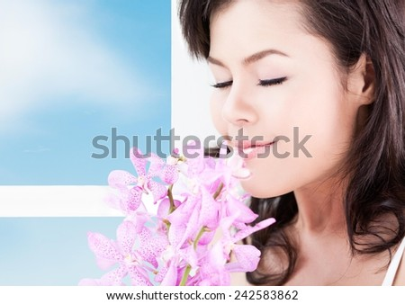 Close up of a young healthy woman smelling flowers. - stock photo
