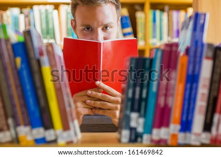 Close up of a young male student holding book in front of his face amid bookshelves in the college library