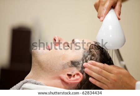 Close-up of a young man having his hair washed in a hairdressing salon - stock photo