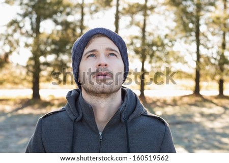 Close-up of a young man in warm clothing looking up in forest on a winter day - stock photo