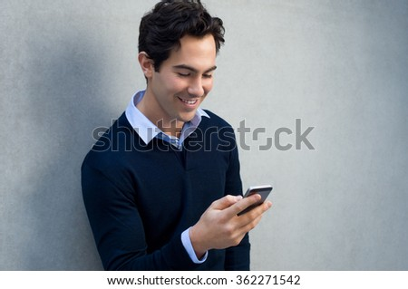 Close up of a young man leaning against a grey wall using mobile phone. Portrait of a happy business man holding a smartphone. Man in casual typing and reading a message on cell phone with copyspace.  - stock photo