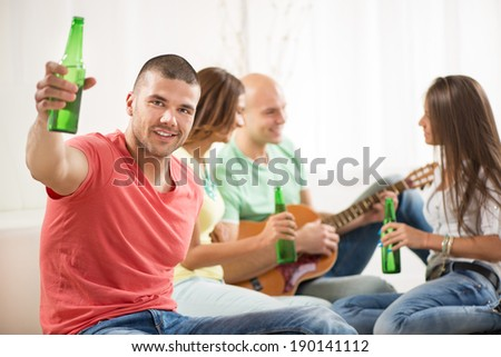 Close up of a young men smiling at home party with beer and cheers. Her friends in the background. - stock photo