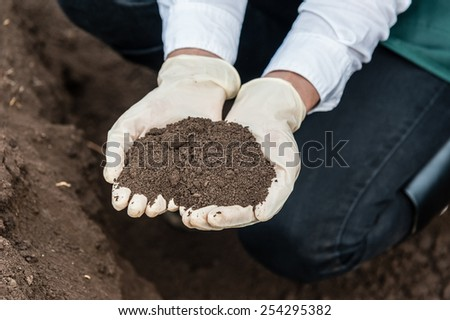 Close-up of a young researcher technician woman hands in greenhouse,in uniform, holding soil . Bio food production.  - stock photo