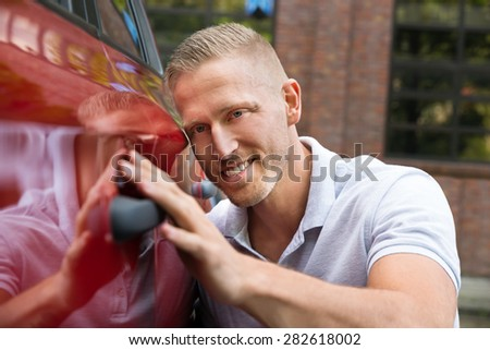 Close-up Of A Young Smiling Man With His New Car
