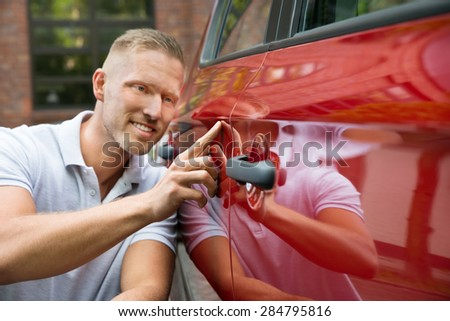 Close-up Of A Young Smiling Man With His New Car - stock photo
